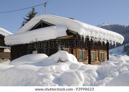 Snow covered house in austrian winter landscape