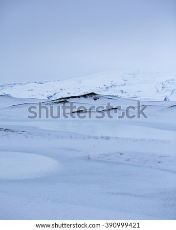 Snow covered lava fields with glacier in background, Vatnajokull national park, Southern Iceland