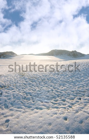 snow covered links golf course in ireland in winter with footprints - stock photo