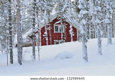 Snow covered log cabin between the trees in Lapland, Finland
