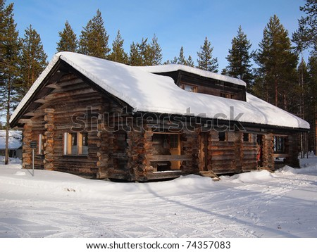 Snow-covered log cabin in a holiday resort in Yllas, Lapland, Finland. - stock photo