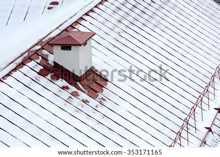 snow covered metal roof of city house viewed from above