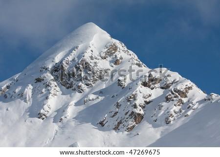 Snow covered mountain peak. European Alps - stock photo