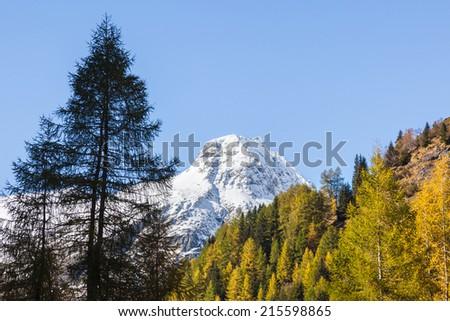 Snow covered mountain peak in autumn - stock photo