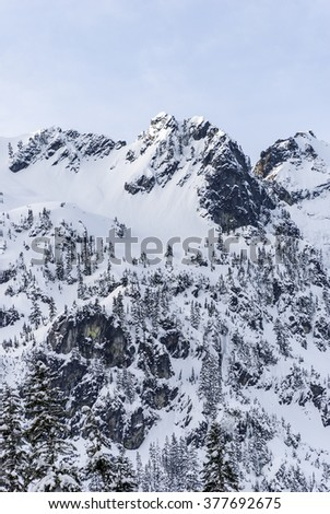 Snow Covered Mountain Peak with Rocky Cliffs - stock photo