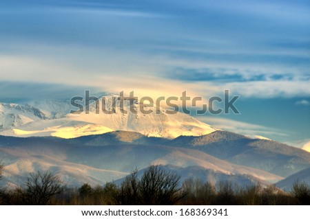 Snow covered mountain peaks in sunset. Location is Tarcu Mountains in Romania