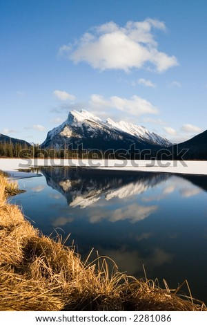 Snow covered mountain reflected in lake - stock photo