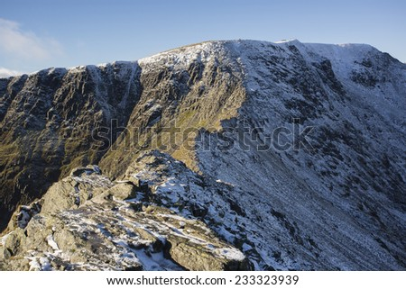 snow covered mountain ridge in the winter sun, striding edge, helvellyn - stock photo