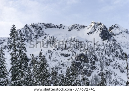 Snow Covered Mountain Ridge with Rocky Cliffs - stock photo