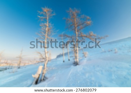 Snow-covered mountain slope with trees. Abstract blur background. - stock photo