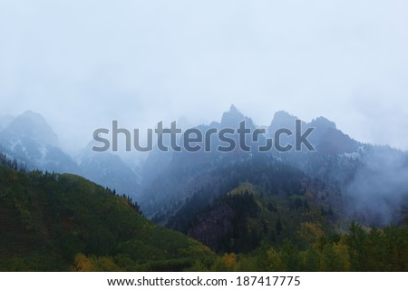 Snow Covered Mountains all around Maroon Bells in fog - stock photo