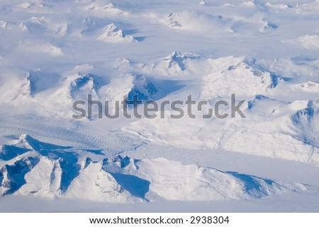 Snow covered mountains and a glacier - the landscape of Greenland. - stock photo