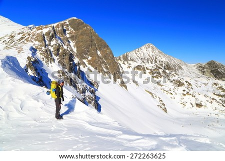 Snow covered mountains and isolated backpacker standing above sunny valley - stock photo