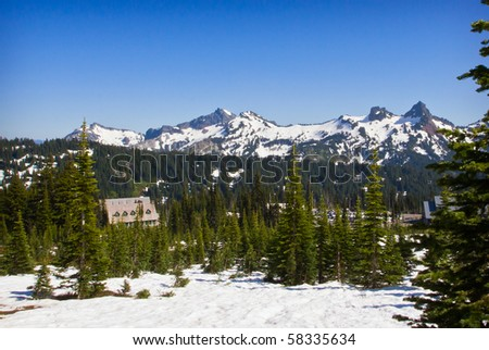 Snow Covered Mountains and resort house under bright blue sky - stock photo