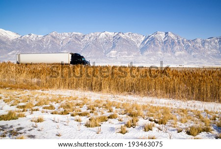Snow Covered Mountains Behind Lakeside Highway Plant Growth Utah Landscape - stock photo