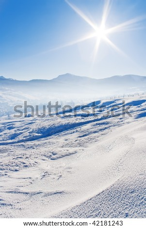 Snow covered mountains under blue sky and shiny sun - stock photo