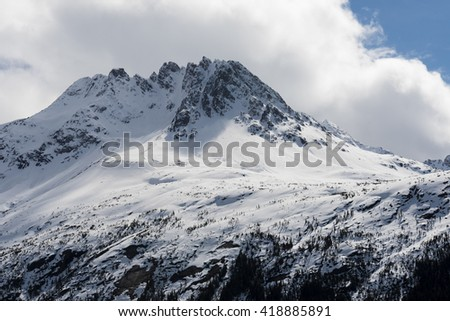 Snow covered mountaintop with white clouds and blue sky in the background - stock photo