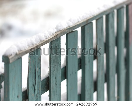 Snow-covered old rural wooden fence. - stock photo