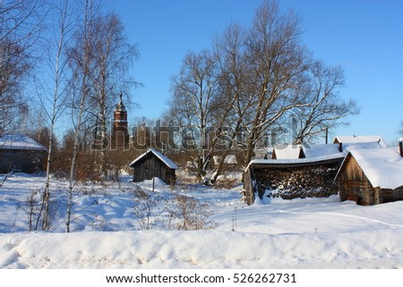 Snow-covered old wooden houses and heaps of firewood in a russian old believer village