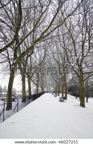 Snow-covered park with trees and benches in England. - stock photo