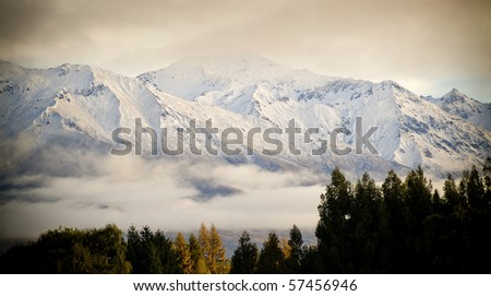 Snow covered peaks wrapped in cloud at sunrise