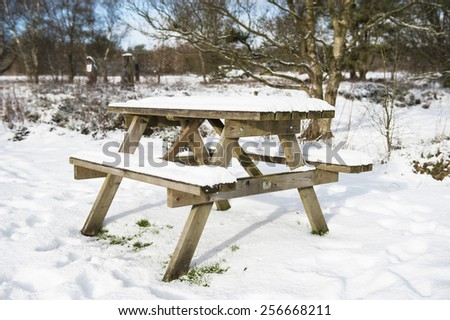 Snow covered picnic bench in rural countryside woodland setting. - stock photo