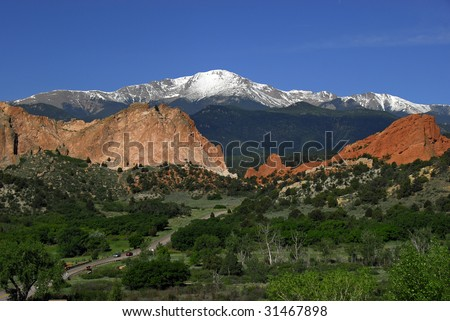 Snow covered Pikes Peak at the Garden of the Gods Park near Colorado Springs, Colorado with two automobiles dwarfed by the spacious landscape - stock photo