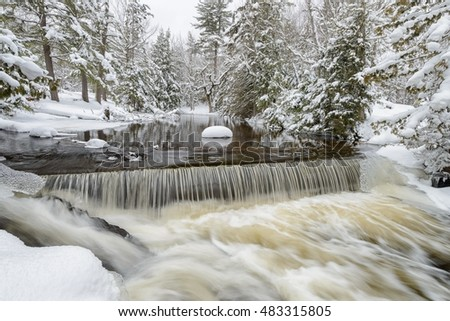 Snow covered pine trees and a pretty waterfall in Michigan's Upper Peninsula.