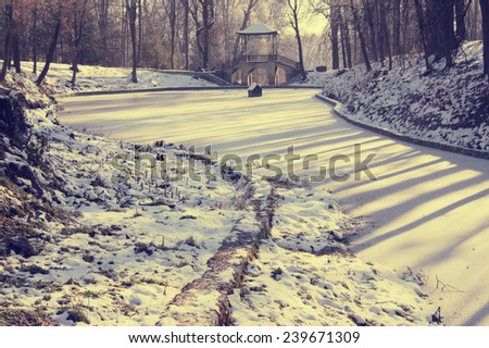 snow-covered pond and stone old bridge in the ancient style of winter park on a sunny day with shadows - stock photo