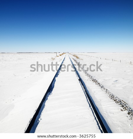 Snow covered railroad tracks leading to a blue sky background. - stock photo