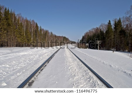 Snow-covered railway line runs through the forest - stock photo