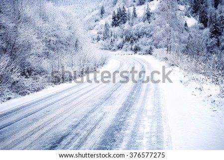 Snow-covered road in forest between mountains - stock photo