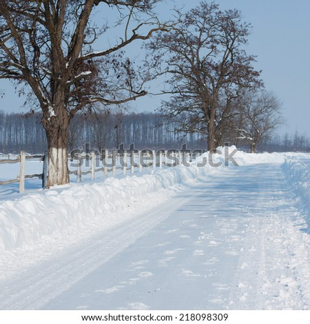 Snow covered road in winter - stock photo