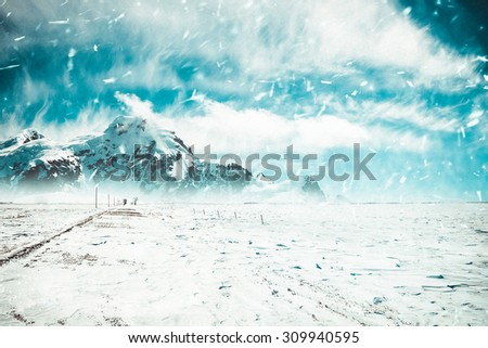 Snow-covered road leaving a mountain landscape - stock photo