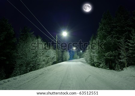 Snow-covered road under the moon - stock photo