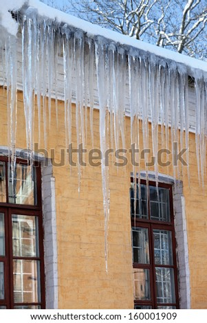 Snow-covered roof with big icicles in winter day - stock photo