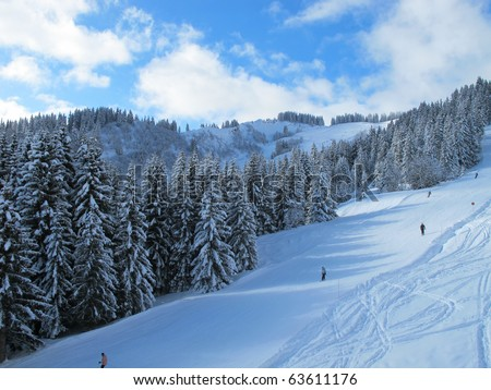 Snow covered ski piste surrounded by trees on sunny day, Combloux French alps France - stock photo