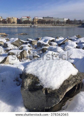 snow covered stones on riverside