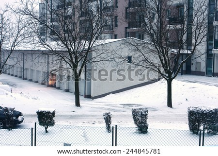 snow covered street and garage - stock photo