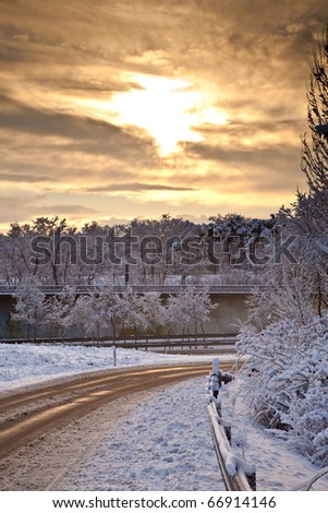 snow covered street in sunrise in wintertime - stock photo