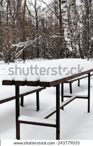 snow-covered table in city park in winter - stock photo