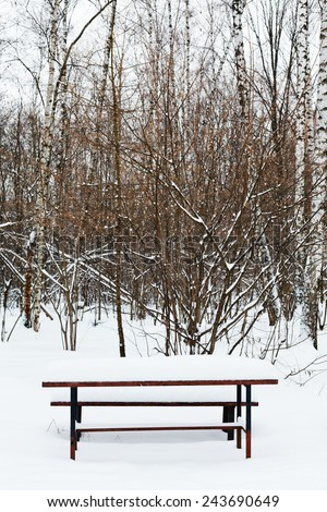 snow covered table on recreation ground of city park in winter - stock photo