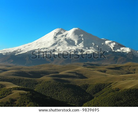 Snow-covered top of Elbrus on a background of the blue sky - stock photo