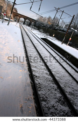 Snow covered train platform with bridge in distance