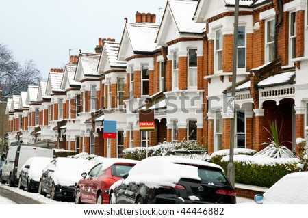"Snow covered Typical English Terraced Houses with ""SOLD"" and ""FOR SALE"" sign in London. - stock photo"