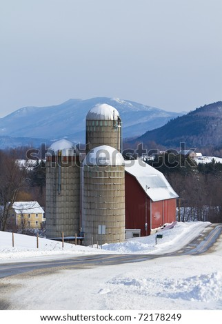 Snow covered Vermont farm nestled in the mountains on an overcast morning - stock photo