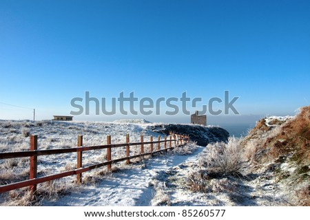 snow covered view of atlantic ocean and castle in ballybunion on a frosty snow covered winters day - stock photo