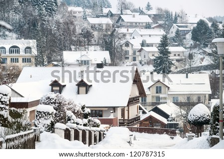Snow covered village and traditional wooden houses in Germany - stock photo