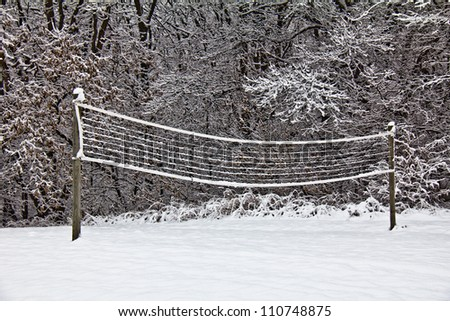 Snow covered volleyball court with wooden posts and net;  snow covered trees in background