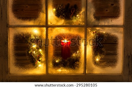Snow covered window with glowing candle and decorative Christmas wreath on window with rustic wood in background. Night time concept.  - stock photo
